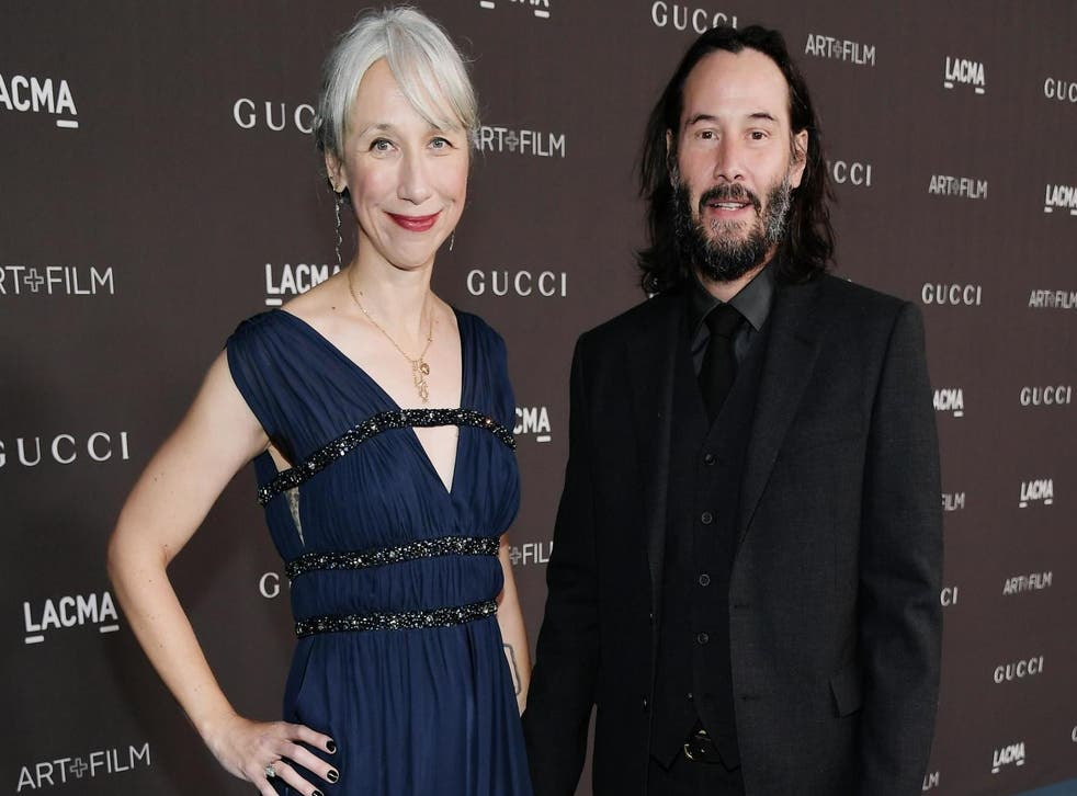 Keanu Reeves holds hands with Alexandra Grant on red carpet (Getty)