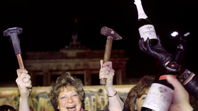 A berliner holds up a hammer and a chisel early on 15 November 1989 in front of the wall at the Brandebourg Gate