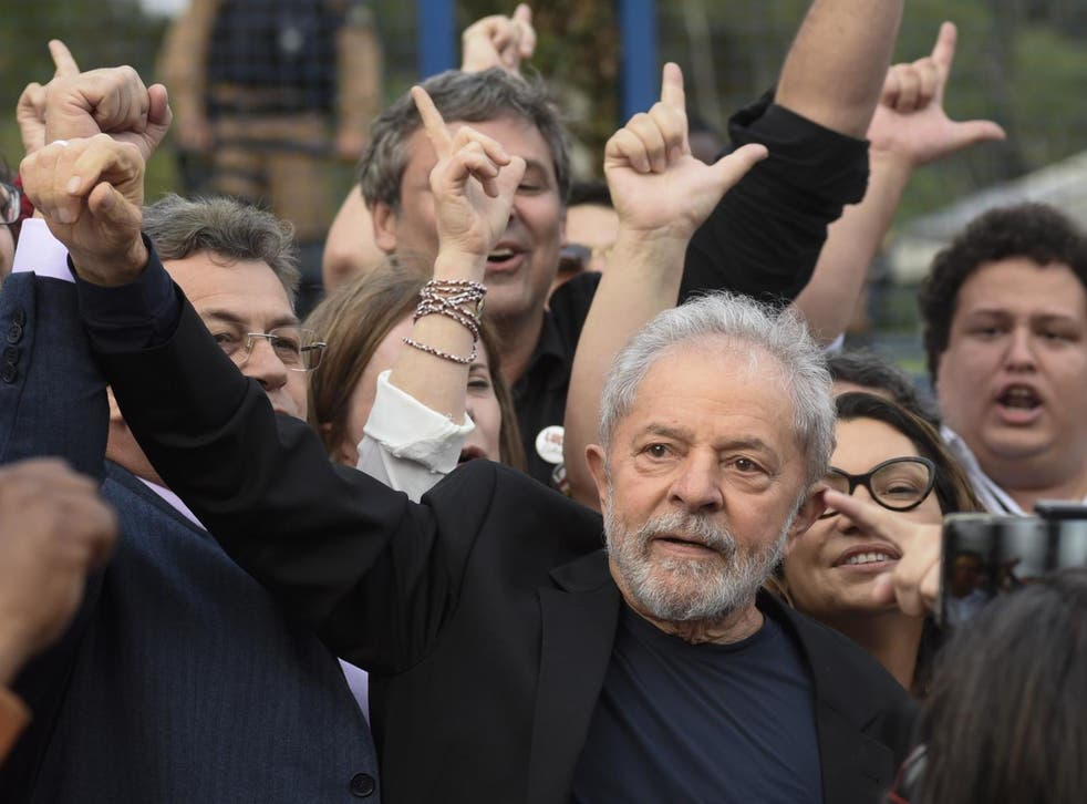Former Brazilian president Lula gestures as he leaves prison, where he had been detained since April 2018
