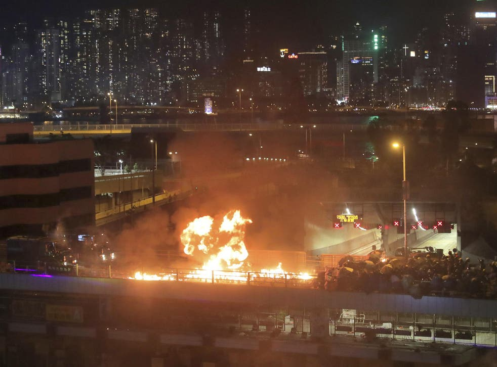 Protesters set alight a bridge separating them from riot police officers