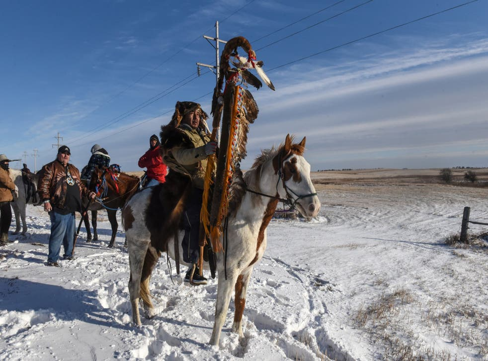 A Lakota member with a sacred staff rides to meet a descendant of the commander of the Wounded Knee massacre