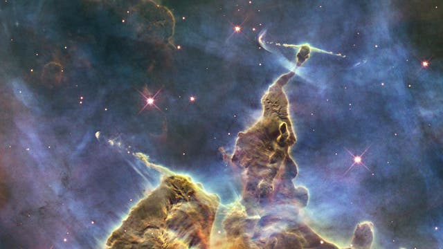 Mystic Mountain, a pillar of gas and dust standing at three-light-years tall, bursting with jets of gas from fledgling stars buried within, was captured by Nasa's Hubble Space Telescope in February 2010