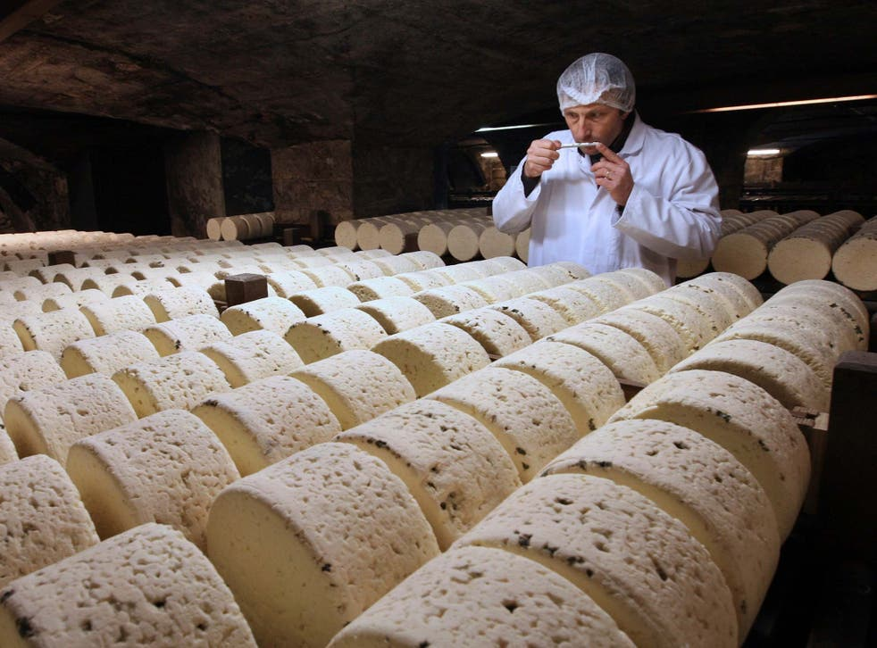 A refiner in a cellar in Roquefort, southwestern France, smells one of the village's eponymous cheeses, which could be hit by new US tariffs