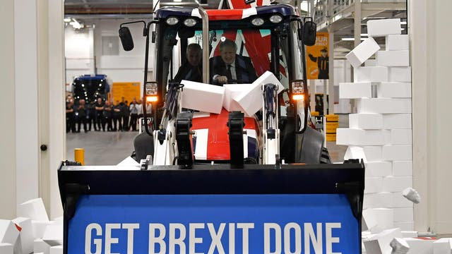 """Boris Johnson drives a Union flag-themed JCB, with the words """"Get Brexit Done"""" inside the digger bucket, through a fake wall emblazoned with the word """"GRIDLOCK"""", during a general election campaign event at JCB construction company in Uttoxeter, Staffordshire"""