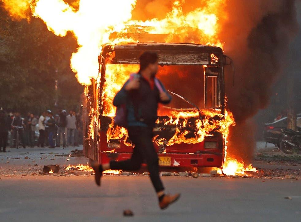 A man runs past a burning bus in New Delhi, India