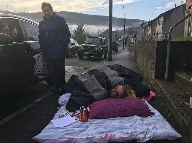 Donna Gilby waiting for an ambulance on the pavement outside her home in Cwmaman