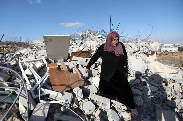 A Palestinian woman checks ruins of a house after it was demolished by Israeli troops in the West Bank village of Khader, near Bethlehem