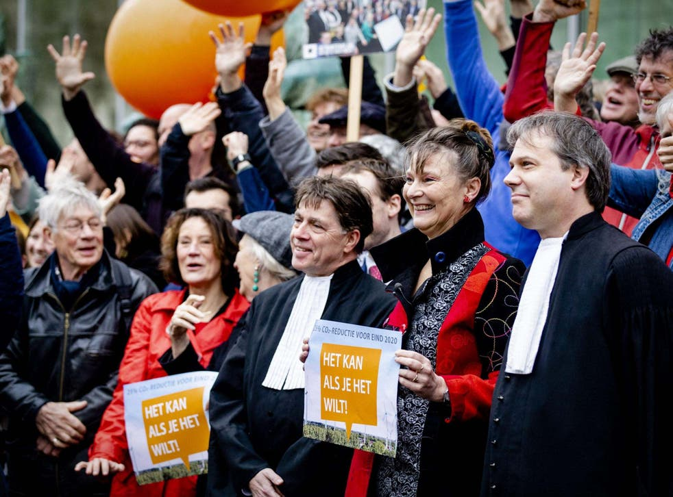 Marjan Minnesma (second on right), director of environment NGO Urgenda, holds a banner outside the Supreme Court prior its ruling in the Urgenda case on 20 December in The Hague