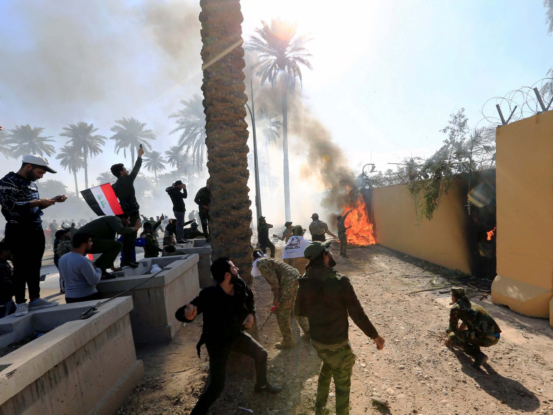 Iraqi protesters break down gate and storm US embassy as gunshots ring out