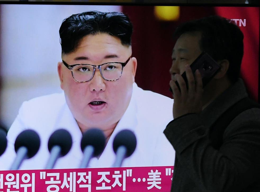 A man walks past a television news program showing the latest pictures of North Korean leader Kim Jong Un, at a railway station in Seoul on December 30, 2019