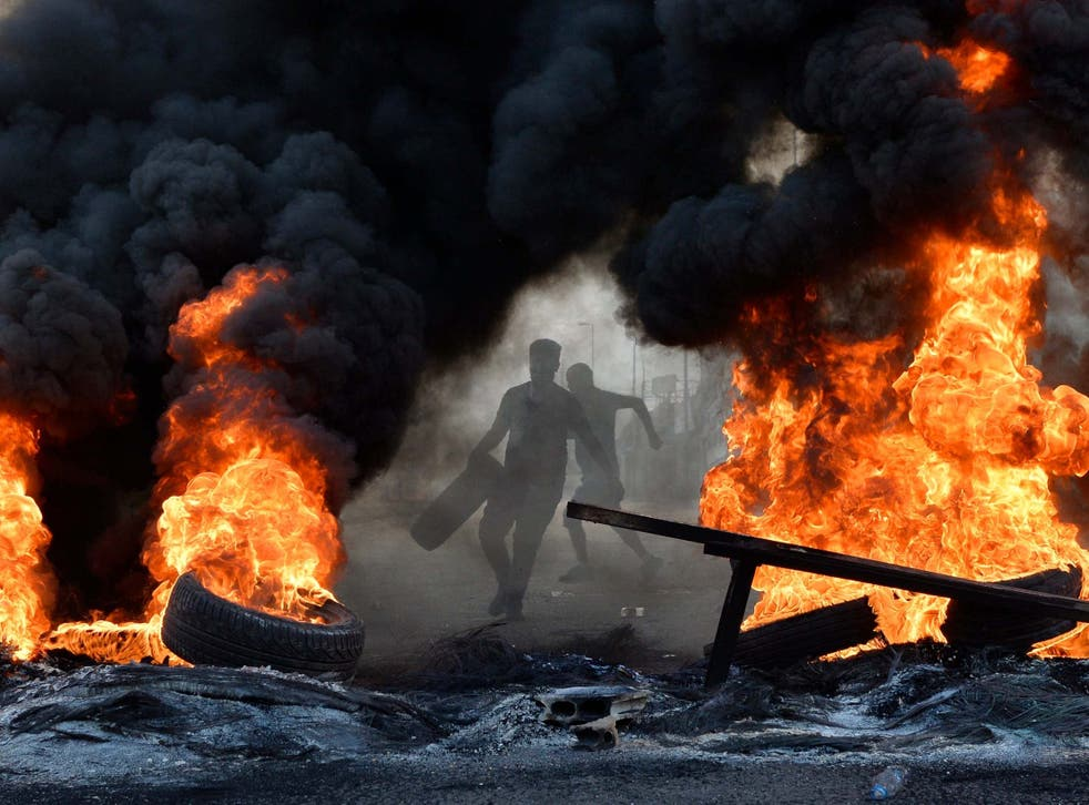 A demonstrator throws a tyre on a fire in Beirut last year