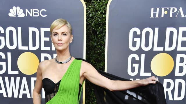<I>Bombshell</I> star Charlize Theron ditched her normally minimalist wardrobe by walking the red carpet wearing a green gown with a contrasting black corset designed by Dior.