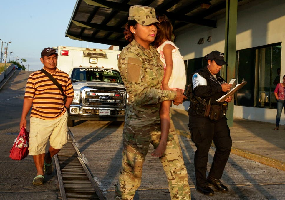 Jose Gonzalez, left, follows his 5-year-old daughter, carried by a police officer, as they leave a hospital in Santiago, Panama. Gonzalez's wife and five of their children are among seven people killed in a religious ritual in the Ngabe Bugle indigenous community