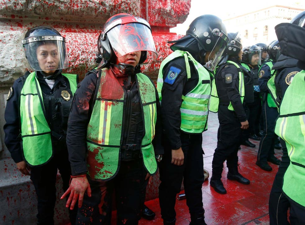 A female police officer covered in red paint stands by during a protest against the deaths of two women in Mexico City