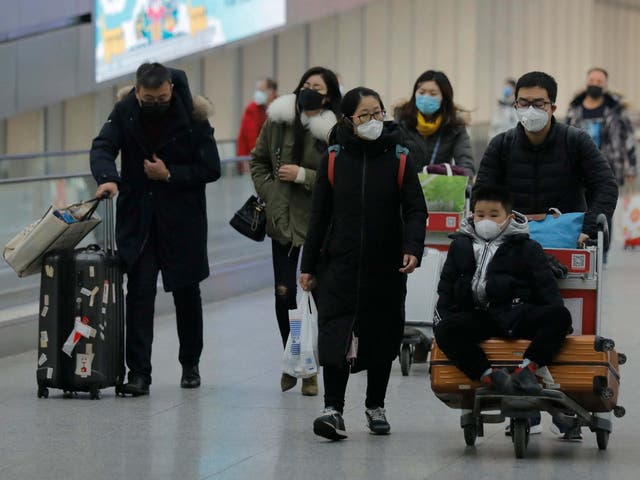 Passengers wearing masks are seen at terminal 3 of Beijing Capital International Airport in Beijing, China, 26 January 2020.