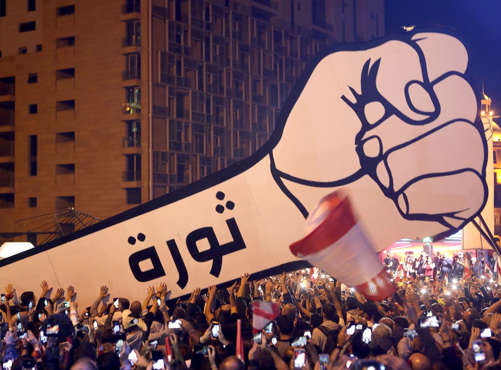 Lebanese protesters raise a giant fist that bears the Arabic word revolution