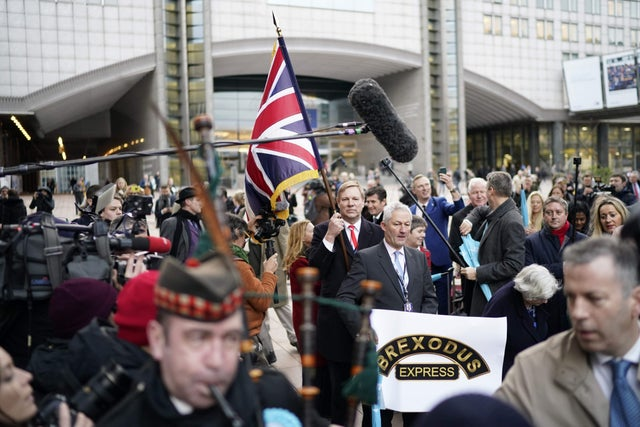 British MEPs Jonathan Bullock, holding the Union Jack flag and Jake Pugh leave the European Parliament, in Brussels on the Brexit day