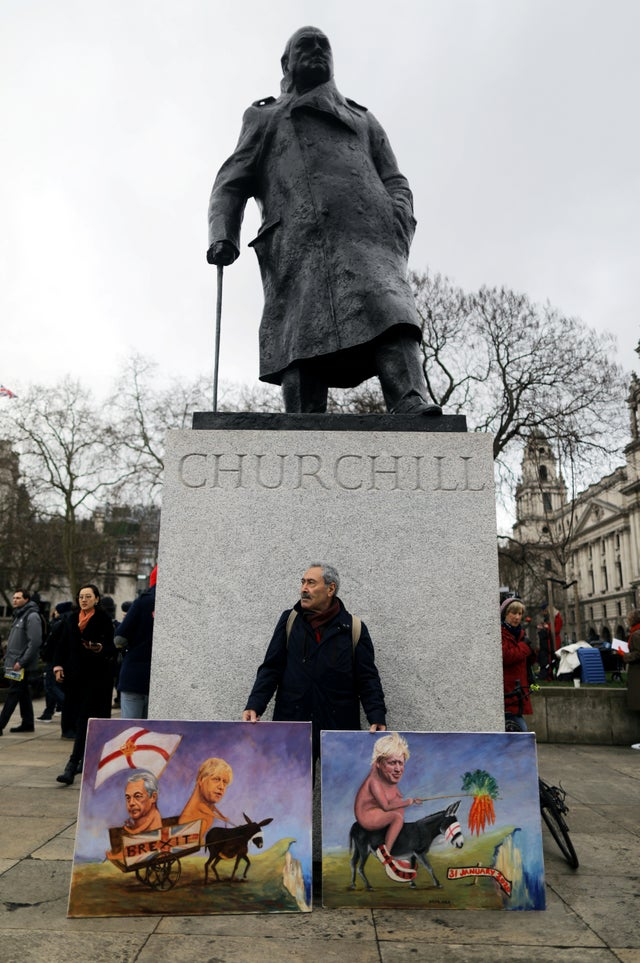 A man poses with paintings on Parliament Square