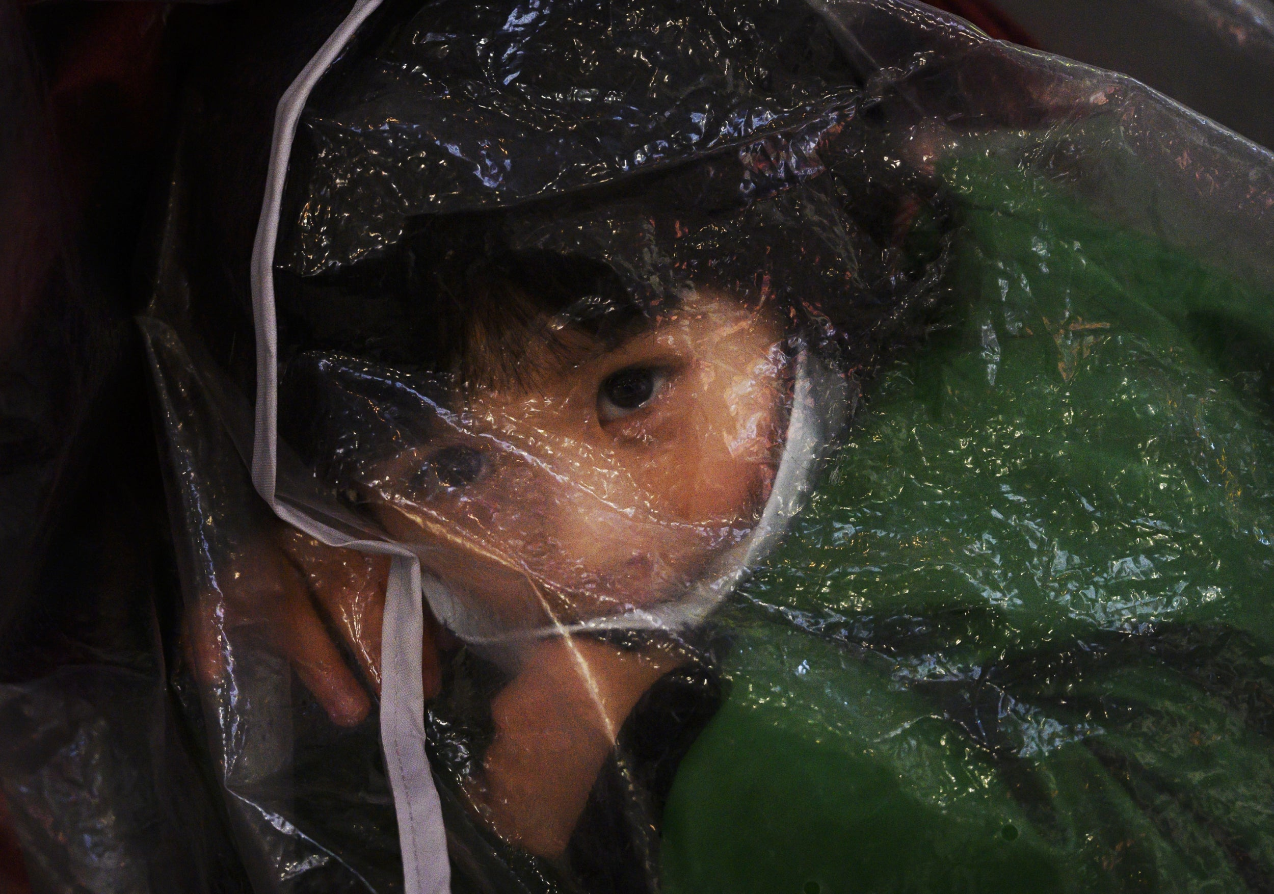 A young child wears a protective mask and is covered in plastic while waiting to check in to a flight at Beijing Capital Airport