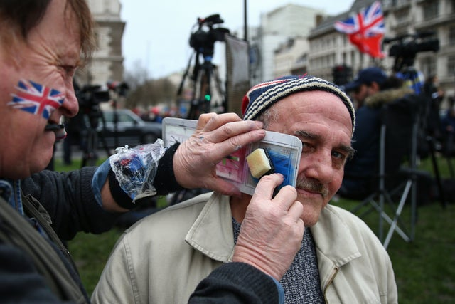 A Pro Brexit supporter has a Union Jack painted onto his face at Parliament Square