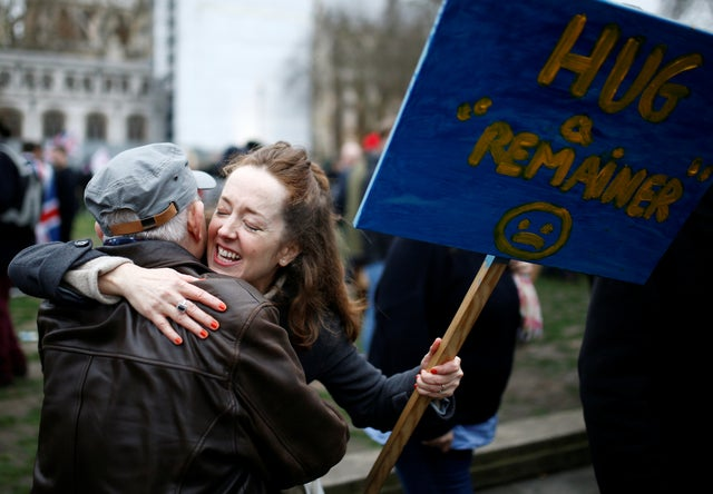 Anti-Brexit protester hugs a man while holding a placard