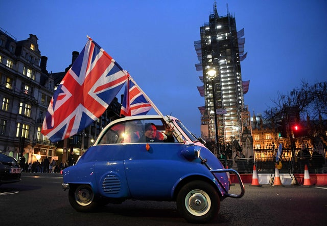 A man waves Union flags from a small car as he drives past Brexit supporters gathering in Parliament Square