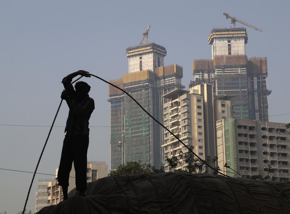 A man works near buildings under construction in Mumbai on 1 February