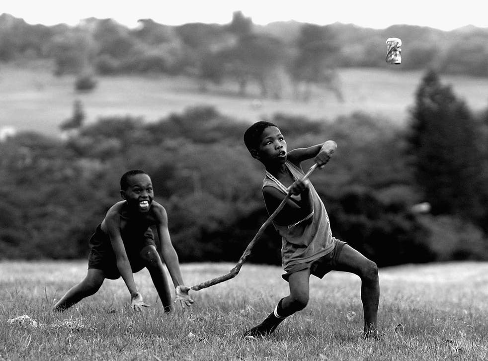 South African children playing cricket with a stick and a Coke can