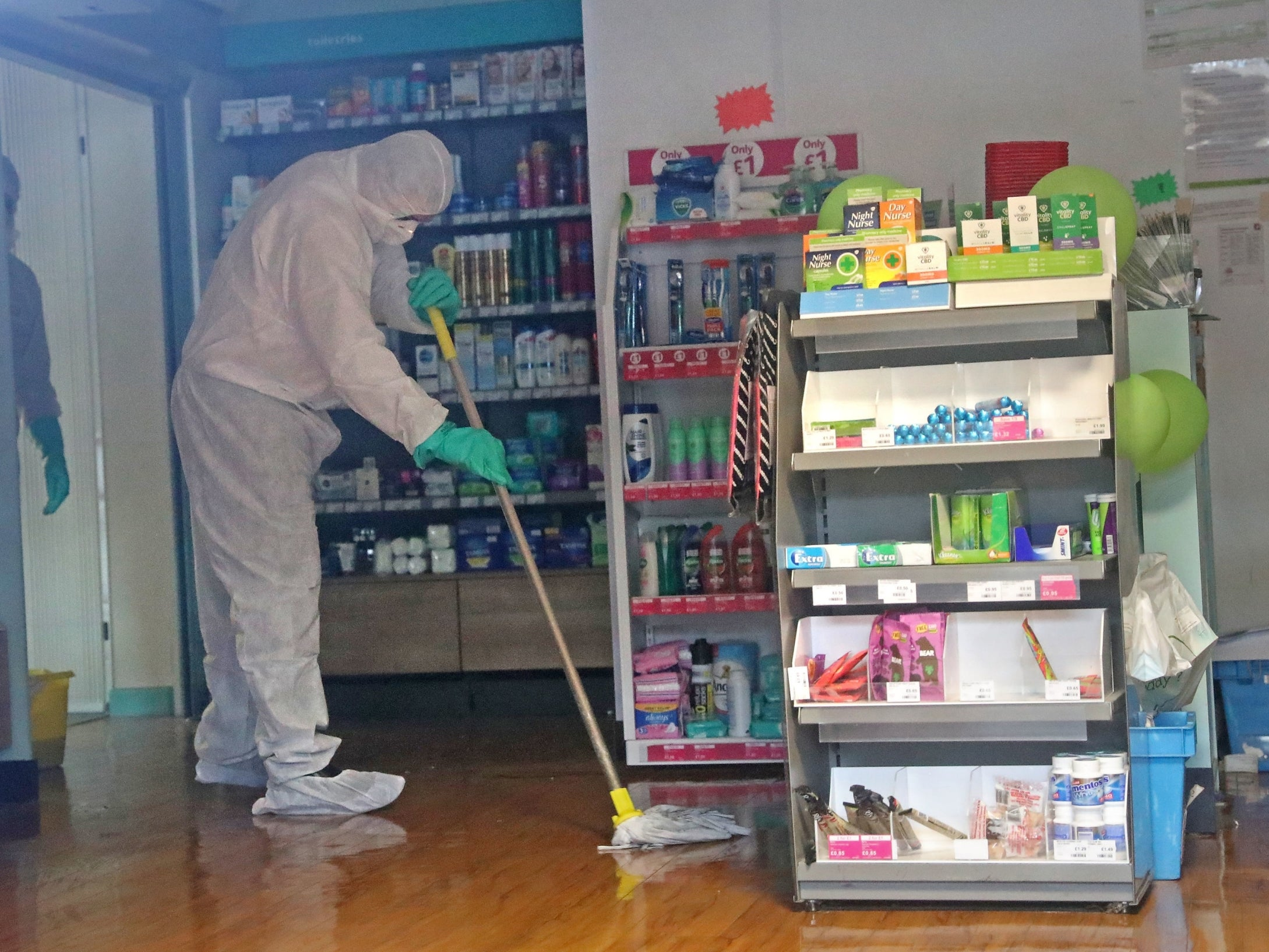 A man in protective clothing cleaning the County Oak Medical Centre GP practice