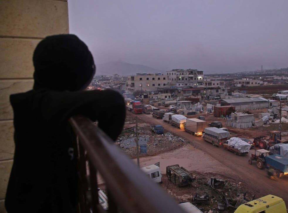 A child in the Syrian town of Dana, east of the Turkish-Syrian border in the northwestern Syrian Idlib province, watches from a balcony as a large convoy of displaced people who fled pro-regime attacks on rebel-held areas of the same province seek shelter in safer parts, on February 11, 2020.