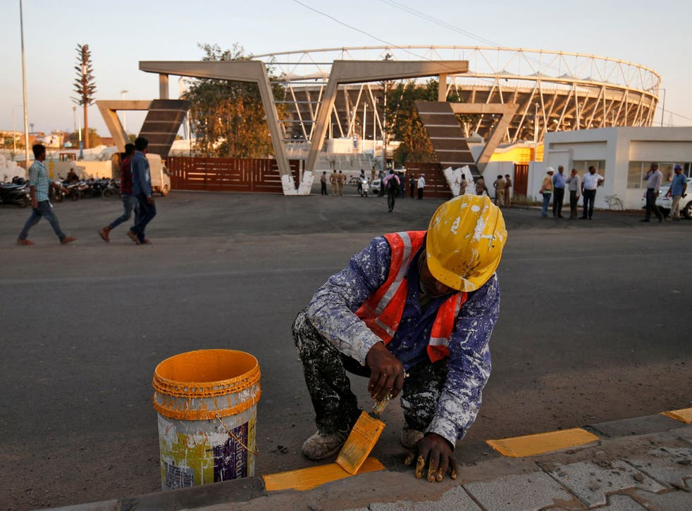 A worker paints a footpath in front of Sardar Patel Gujarat Stadium, where Donald Trump is expected to visit during his upcoming trip to India, in Ahmedabad