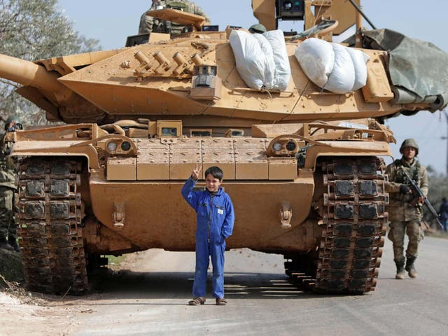 A Syrian boy stands in front of a Turkish military vehicle east of Idlib city in northwestern Syria on February 20, 2020