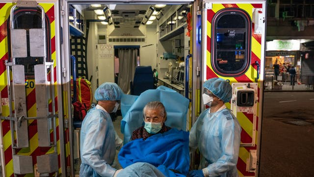 Paramedics wearing personal protective equipment carry patient on a stretcher on to an ambulance in North Point district in Hong Kong, China