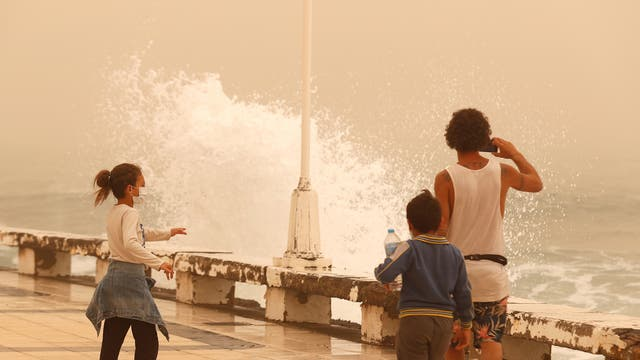 """A family watches the waves during a sandstorm locally known as """"calima"""""""