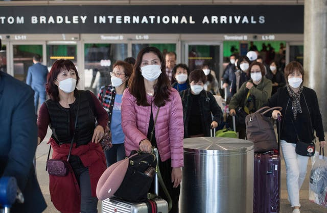 Passengers on a flight from Asia arrived to Los Angeles International Airport waring face masks. US health officials recommend people to only wear masks if they are sick