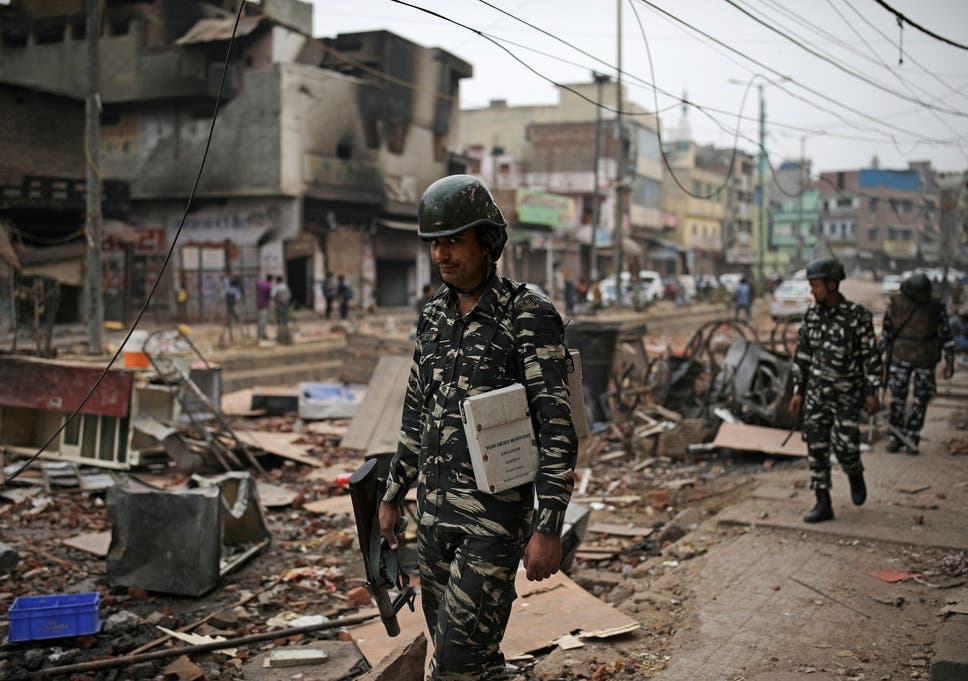 Indian paramilitary soldiers patrol streets vandalised in the religious violence on Thursday in Delhi