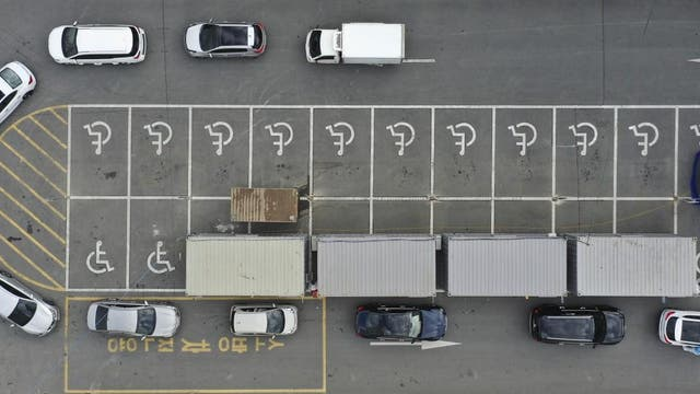 """Visitors with suspected symptoms of the new coronavirus, inside of a car, bottom right, get virus test by members of medical team as others queue in their cars at a """"drive-through"""" test facility at Yeungnam University Medical Center in Daegu on 27 February 2020"""