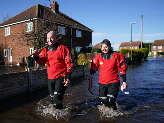 Members of Humber Fire and Rescue Service walk through flood water after the River Aire bursts its banks in East Cowick, Yorkshire, on 29 February 2020.