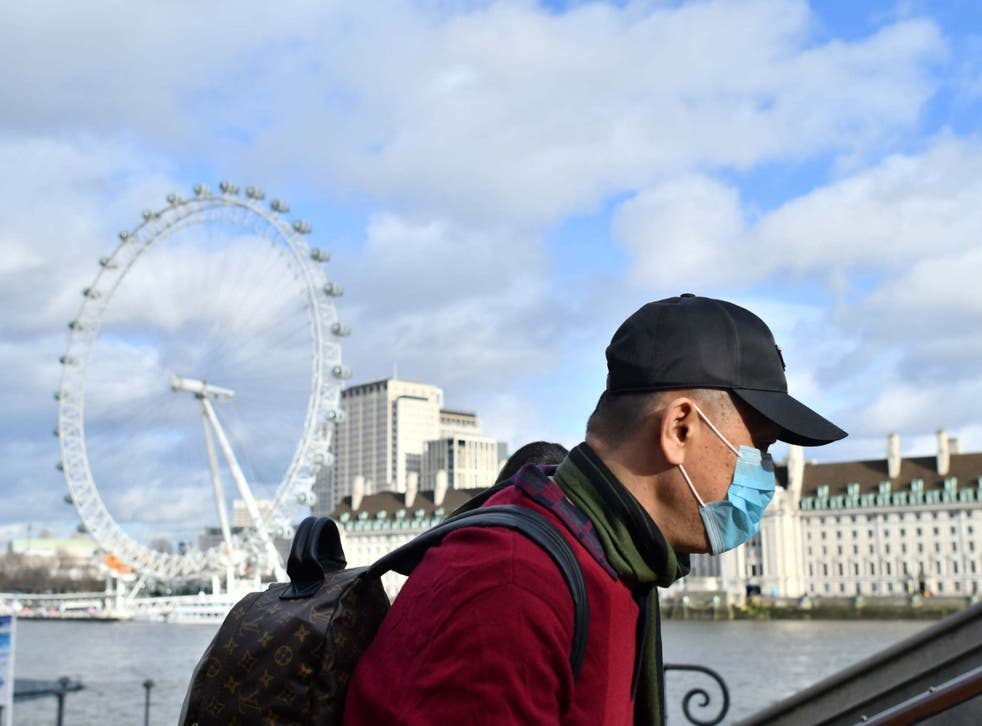 A man wears a face mask as he walks along the Thames embankment in central London