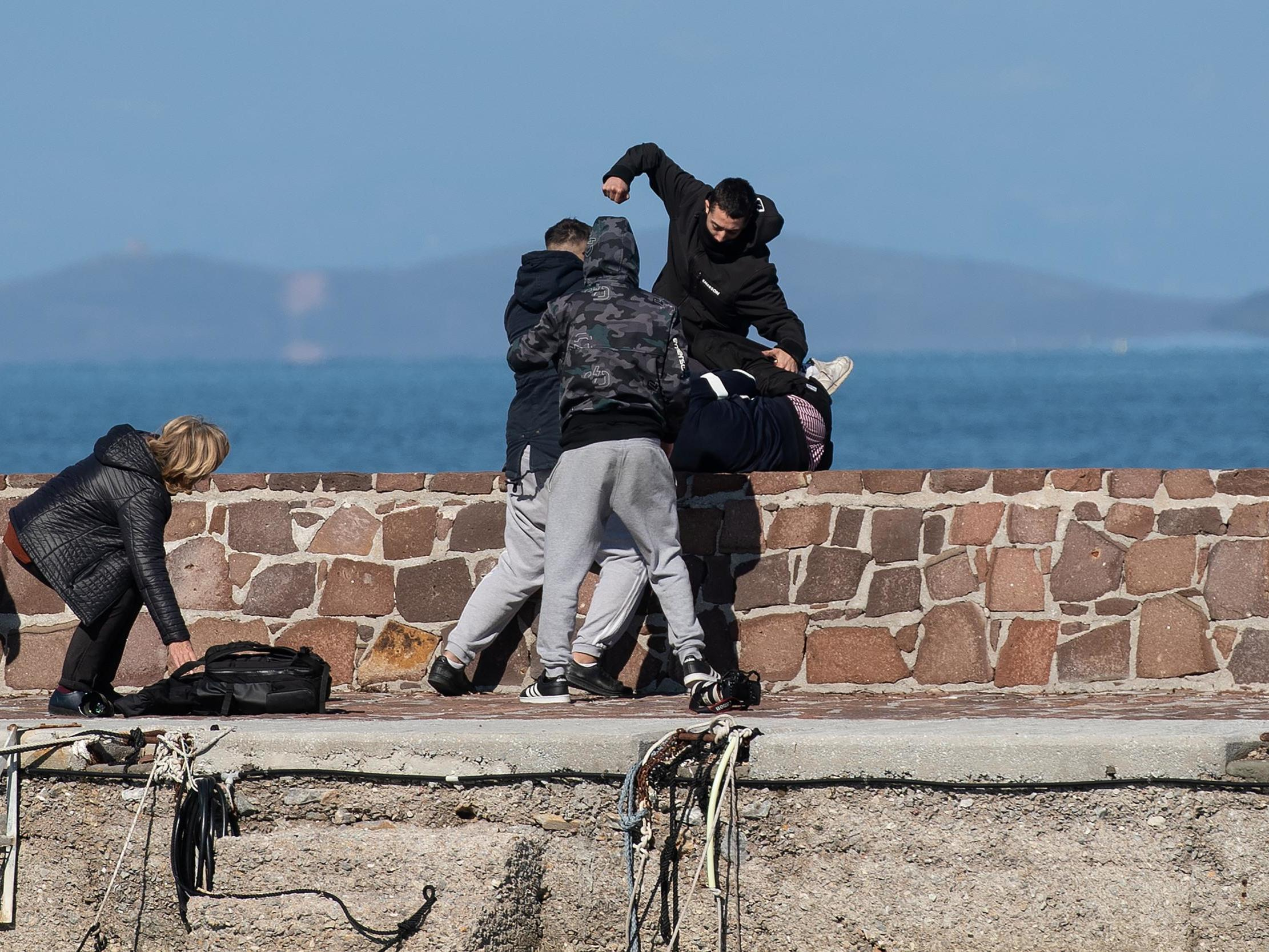 Locals attack journalists and try to stop migrants disembarking on Greek island