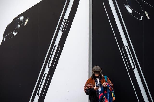 A man checks his phone next to billboards advertising the an Apple iPhone 7 smartphone as he stands on Oxford Street in London on March 7, 2017