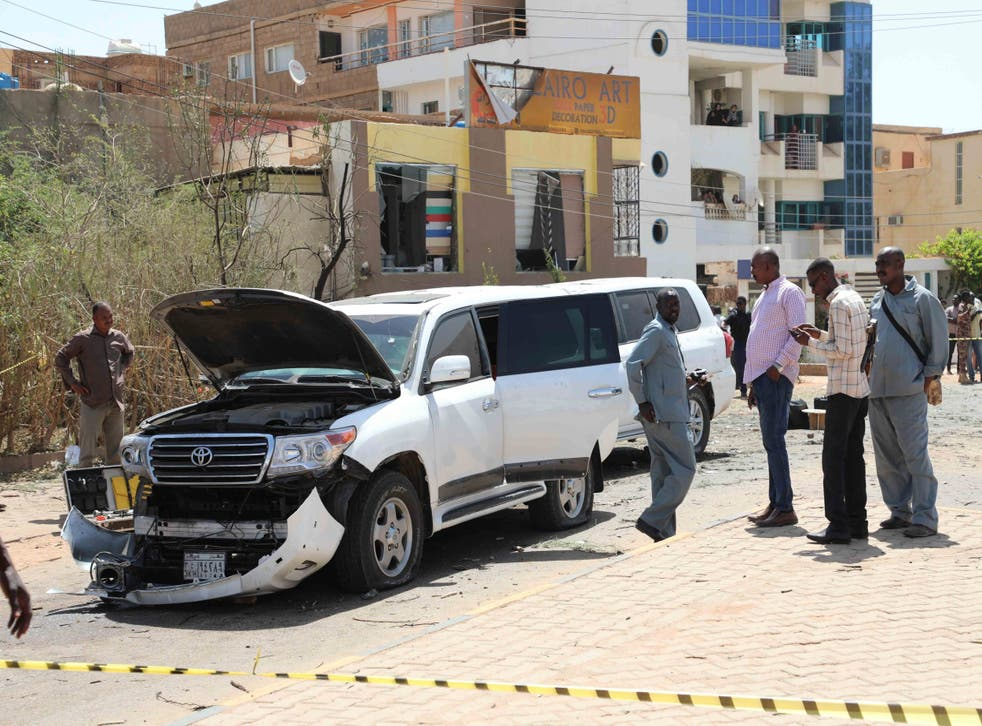 Sudanese police officers assess the damage after an explosion went off near the Sudanese prime minister's convoy