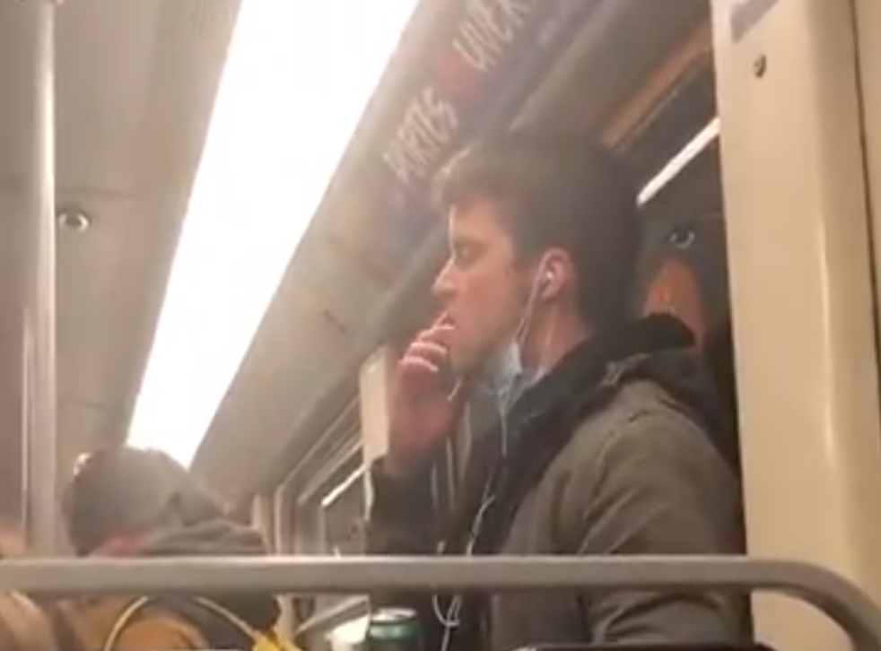 A man who was filmed licking his fingers and wiping them on a handrail on public transport was arrested by Belgian authorities