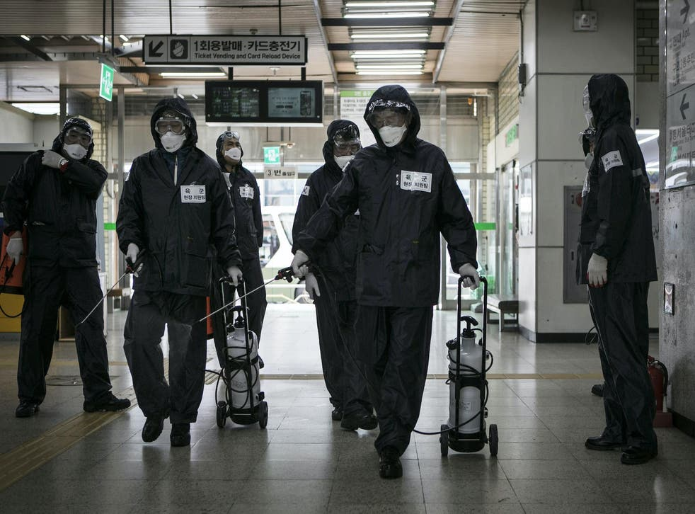 Members of the reserve forces, wearing protective gear, spray antiseptic solution to guard against the coronavirus (COVID-19) at the metro station on March 12, 2020, in Seoul, South Korea