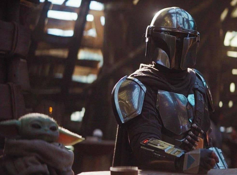 The Mandalorian (Pedro Pascal) sits with a tiny green companion in Disney's new Star Wars spin-off