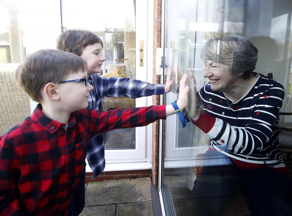 Ben and Isaac talk to their grandmother Sue through a window, as she and her husband Alan self-isolate at their home in Cheshire