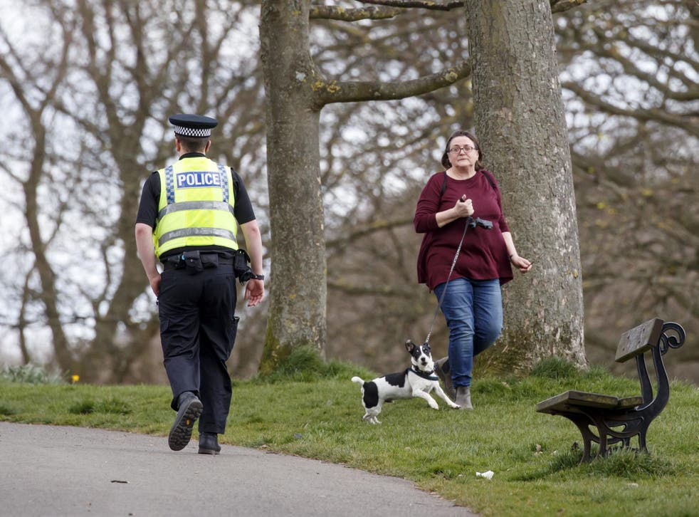A policeman walks past a woman exercising with dog in Roundhay Park, Leeds