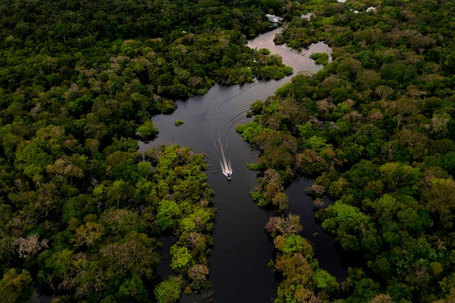 Aerial view showing a boat speeding on the Jurura river in the municipality of Carauari, in the heart of the Brazilian Amazon Forest, on March 15, 2020. - Many young people in the heart of the Amazon rainforest choose their community over the city.