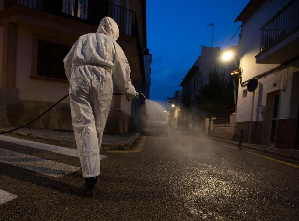 A volunteer farmer caries out a disinfection in the town of Sant Jordi, on the Balearic island of Mallorca on 10 April, during a national lockdown to prevent the spread of the COVID-19 disease