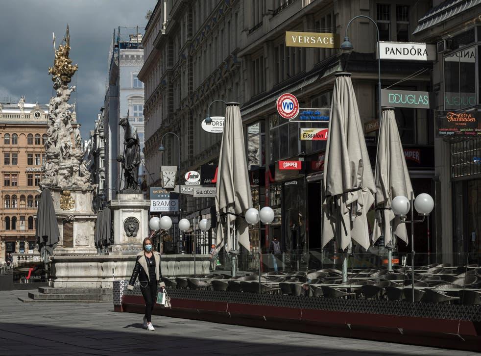 A woman wearing a face mask walks through downtown Vienna, Austria